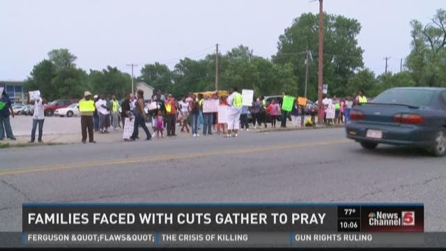 Families faced with cuts gather to pray